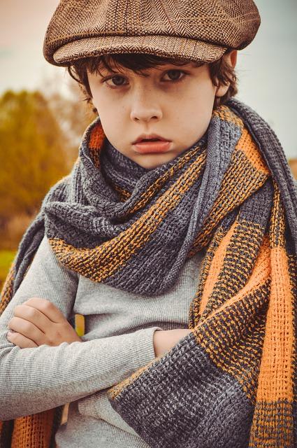 ハイゲージセーターを着てストールを巻きこちらを見つめる少年